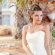 Young bride near palm-tree - Foto Stock