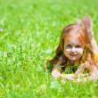 Royalty-Free Stock Photo: A smiling girl is lying on the meadow
