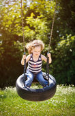 Little girl is swinging — Stockfoto