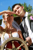 Wedding couple with steering wheel — Stock Photo