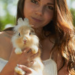 Beautiful young girl holding a bunny — Stock fotografie