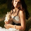 Beautiful young girl holding a bunny — Stock Photo #11239999