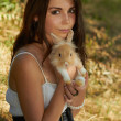 Beautiful young girl holding a bunny — Stock Photo #11240013