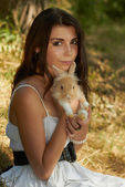 Beautiful young girl holding a bunny — Stock Photo