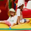 Stock Photo: Cute little sisters in jumping castle