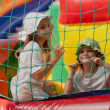 Cute little sisters in a jumping castle — Stock Photo #11375537