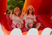 Cute little sisters in a jumping castle — Stock Photo