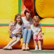 Stock Photo: Mother and her daughters sitting on jumping castle