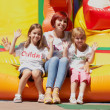 Mother and her daughters sitting on bouncing castle - Stock Photo