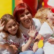 Mother and her daughters having fun on jumping castle - Stock Photo