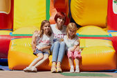 Mother and her daughters sitting on jumping castle — Stock Photo