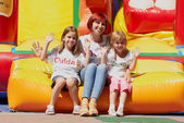 Mother and her daughters sitting on bouncing castle — Stock Photo