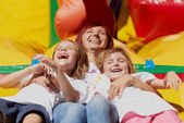 Mother and her daughters having fun on jumping castle — Stock Photo