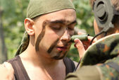 Soldiers putting on face paint — Stock Photo