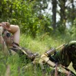 Soldier takes rest lying on a grass - Stock Photo