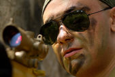 Soldier in sunglasses targeting with a gun — Stock Photo