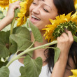 Girl playing with sunflowers in field — Stock Photo