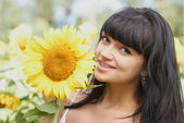 Smiling girl with sunflower outdoors — Stock Photo