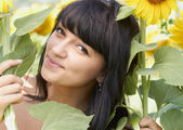 Young girl with sunflowers outdoors — Stock Photo