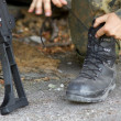 Soldier lacing his boots - Stock Photo