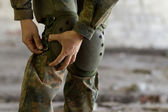 Soldier puts knee pads on — Stock Photo