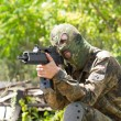 Terrorist with a gun outdoors — Stock Photo