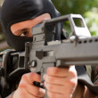 Stock Photo: Terrorist in black mask with a gun