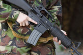 Soldier holding automatic rifle — Stock Photo
