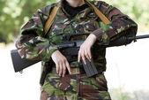 Female soldier holding a gun — Stock Photo