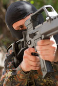 Soldier in black mask with a gun — Stock Photo