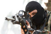 Terrorist in black mask with a gun — Stock Photo