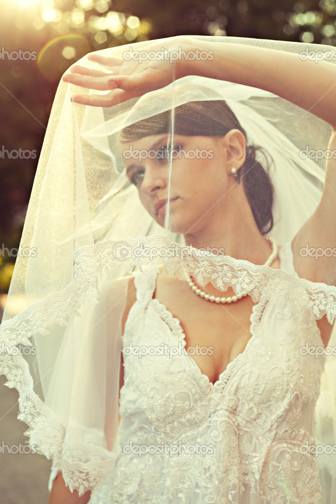 Beautiful bride in wedding dress in sunlight outdoor — Stock Photo #11349096