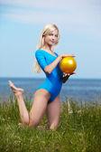 Blonde girl gymnast outdoors — Stock Photo