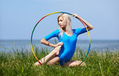 Blonde girl gymnast outdoors — Stock Photo