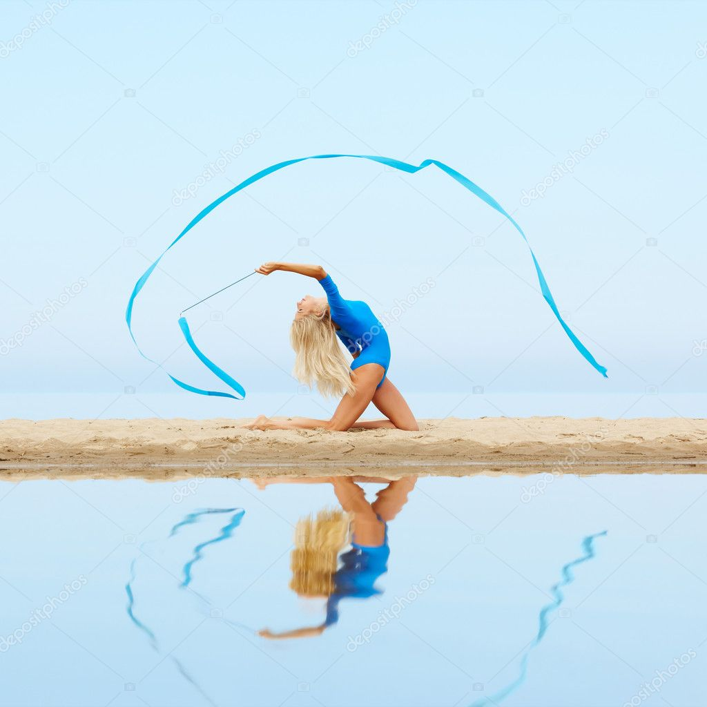 Outdoor portrait of young beautiful blonde woman gymnast exercising with ribbon on the beach — Stock Photo #11564988