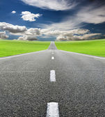 Green field and road over blue sky — Stock Photo