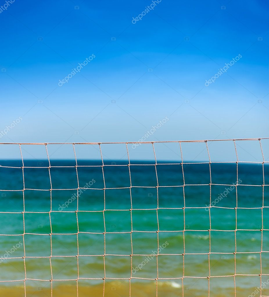 Close up shot of fishing or volleyball net over blue sky and sea waves — Stock Photo #12291820