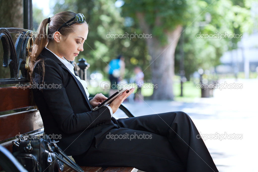 Businesswoman on bench in park  Stock Photo #11347787