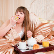 Woman eating breakfast and drinking coffee in bed. Young woman s — Stock Photo #11349793
