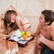 Happy man and woman having luxury hotel breakfast in bed togethe — 图库照片