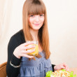 Young woman sitting at table having breakfast, drinking orange j — Stock Photo