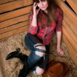Stock Photo: Beautiful smiling cowgirl in hay