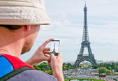 Tourist taking a picture of the Eiffel Tower in Paris — Stock Photo