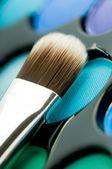 Multicolored eye shadows with cosmetics brush — Stock Photo
