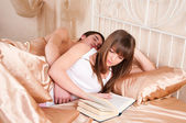 Woman reading a book and man sleeping next to her. — 图库照片