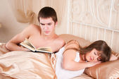 Man reading a book and woman sleeping next to her. — Stock Photo
