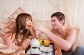 Happy man and woman having luxury hotel breakfast in bed togethe — Stock Photo