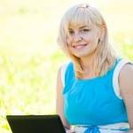 güzel bir genç kadın dizüstü bilgisayar ile bir parkta çim üzerinde oturur. — Stok fotoğraf