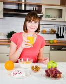 Young woman drinking orange juice at home — Stock Photo