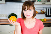 Young happy woman with orange — Stock Photo